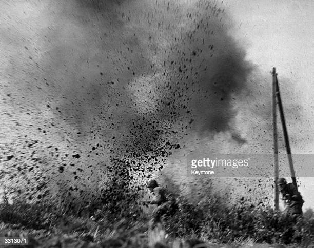 American paratroopers dash through a field in an assault on Arnhem, Holland, amidst exploding German shells.