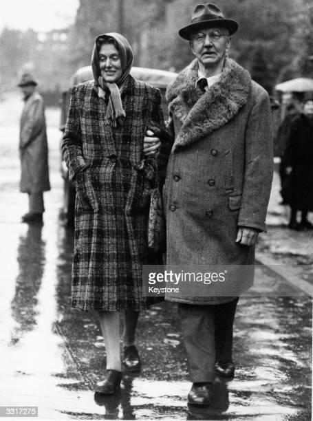 German financier Dr Hjalmar Schacht in Nuremberg in the rain with his wife after his release