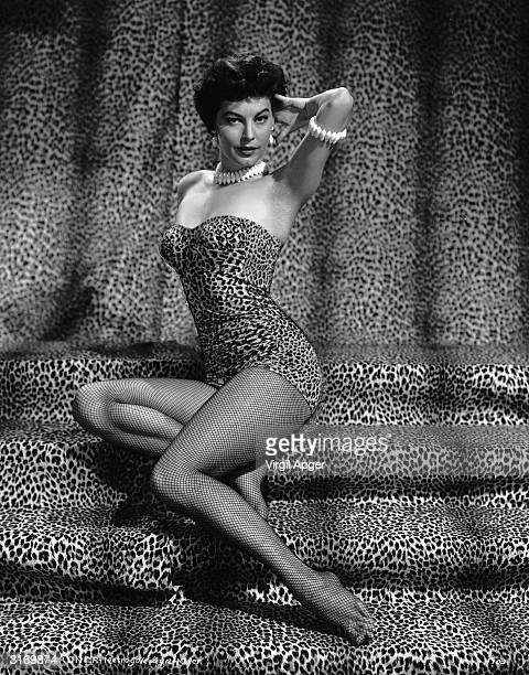 Actress Ava Gardner poses on a flight of steps draped in leopard print cloth wearing a matching body suit