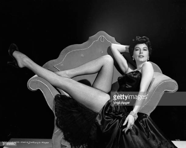 American actress Ava Gardner shows off her famous legs in a pair of fishnet stockings.