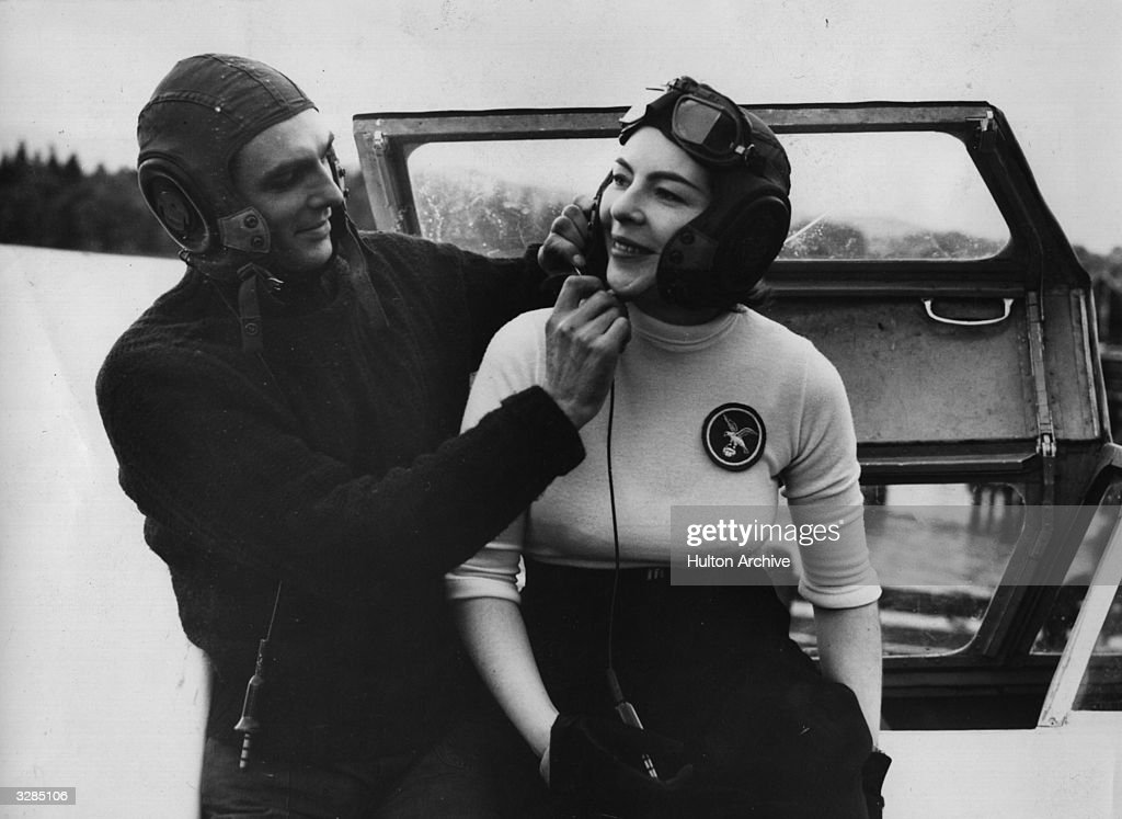 Portrait of Mr Hanning adjusting the strap of his wife's helmet in the cockpit of their jet-propelled speedboat 'White Hawk' on Lake Windermere, where they are preparing to make an attempt on the world's water speed record of 178mph.