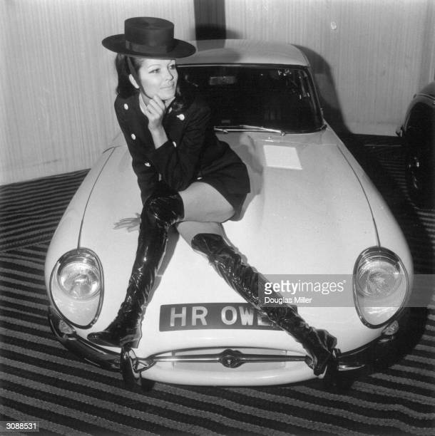 Posed on the bonnet of a Jaguar 22 fixed head coupe Petra Shoshina models a pure worsted black dress and military style coat