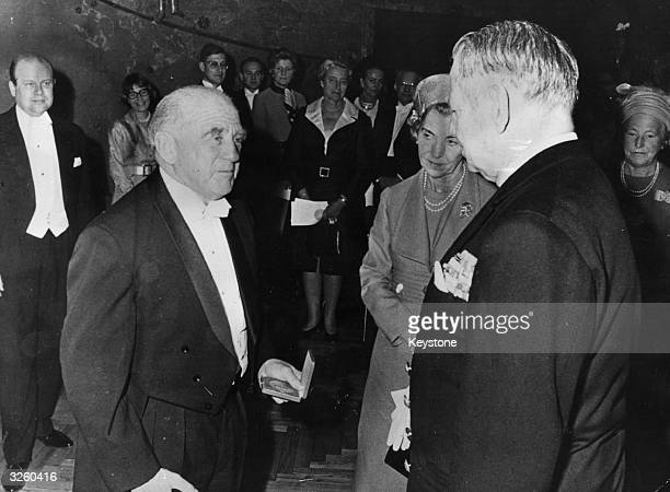 Professor Werner Karl Heisenberg the German physicist chatting to King Frederick and Queen Ingrid of Denmark after being formally presented with the...