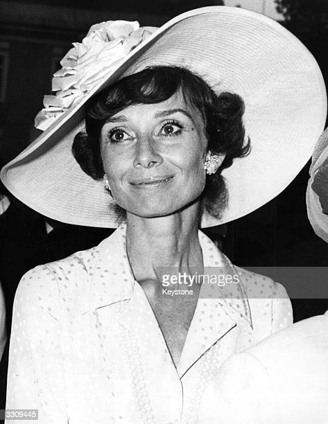 Film actress Audrey Hepburn resplendant in widebrimmed hat attends a wedding