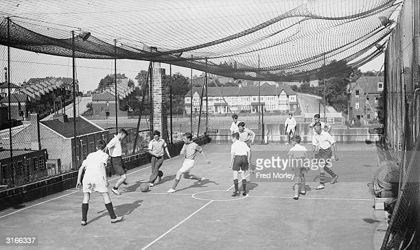 Boys from the Hornsey Young Men's Christian Association club play football on the roof of their clubhouse in London