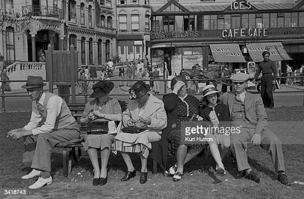 A group of holidaymakers enjoying the sun on a seaside bench on the Isle of Man Original Publication Picture Post 196 The Isle of Man pub 1939