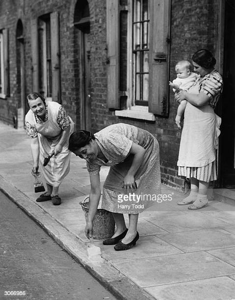 Housewives of Roupell Street London painting kerbs white to help night time traffic during WW II