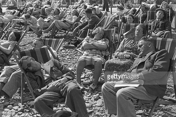 People relaxing on deckchairs on a crowded beach on the Isle of Man Original Publication Picture Post 196 The Isle Of Man pub 1939