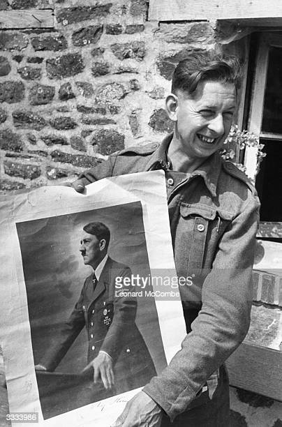 A British soldier in Normandy grimaces as he holds up a portrait of Hitler Original Publication Picture Post 1797 The Road To Victory pub 1944