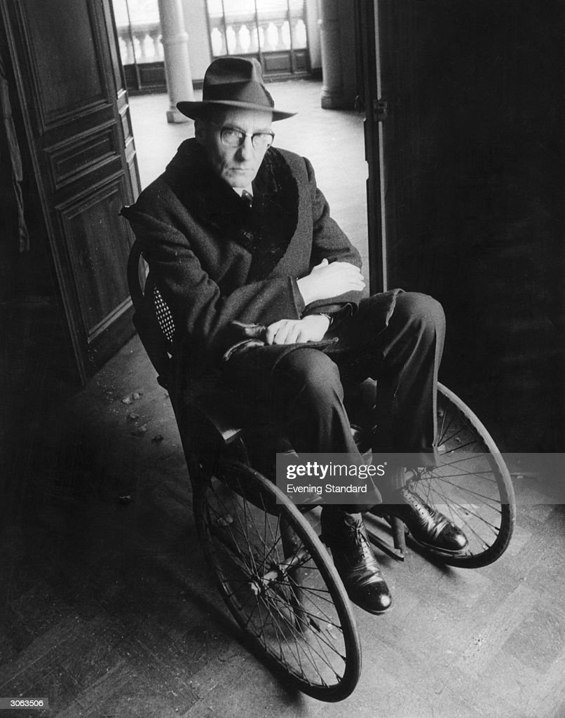 American writer William S Burroughs (1914 - 1997) sitting in a wheelchair.