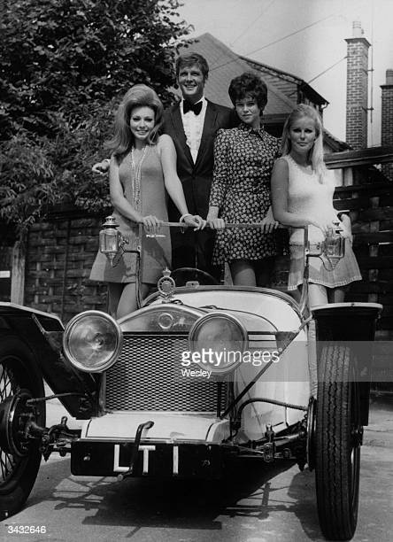 Film star Roger Moore ex star of the TV series 'The Saint' aboard a car made specially for his new film 'Crossplot' With him are his costars l to r...