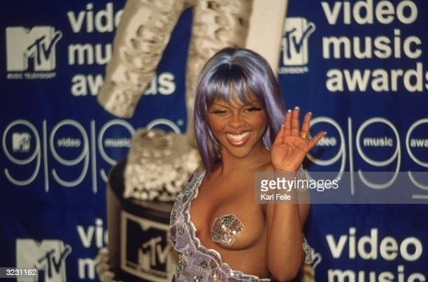 Rap artist Lil' Kim wearing a revealing purplesequined dress with pasties waves to the camera at the MTV Video Music Awards at the Metropolitan Opera...