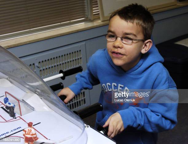 9yearold Caleb Schroeder plays table hockey in Marnie's Lounge at Sick Kids hospital as part of a media meet and greet Thursday morning At three...