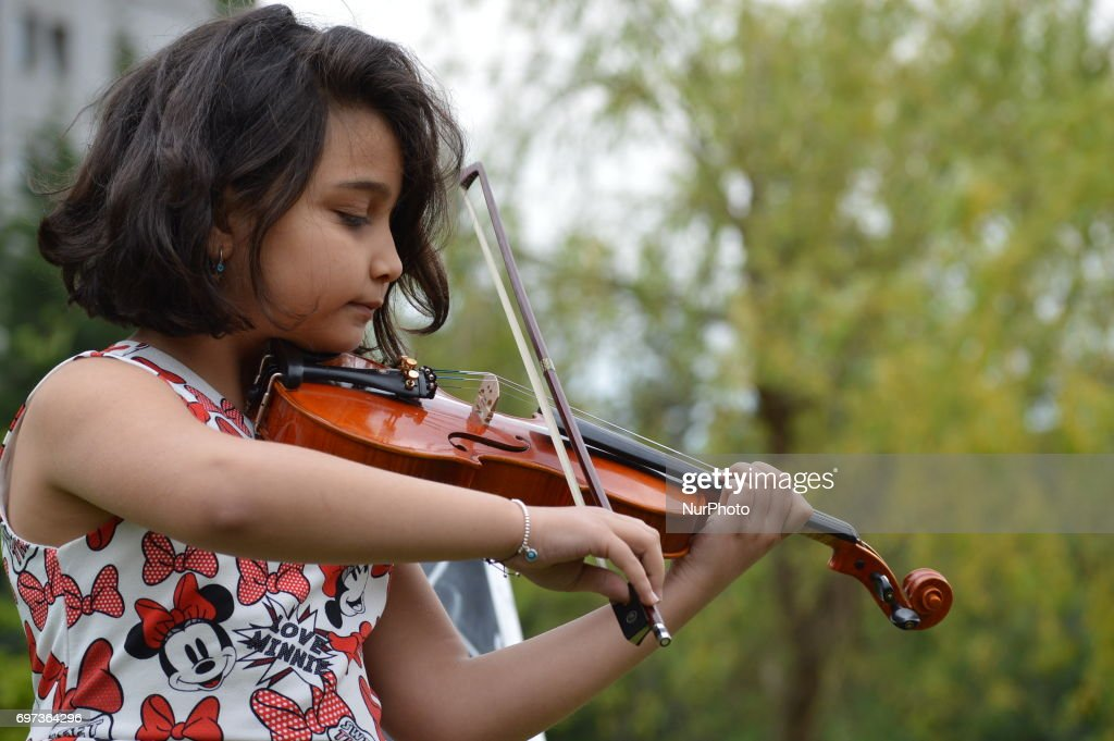9-year-old Defne (Last name not given) plays violin after an outdoor lecture on 'Post-truth' at the park in Ankara, Turkey on June 18, 2017.