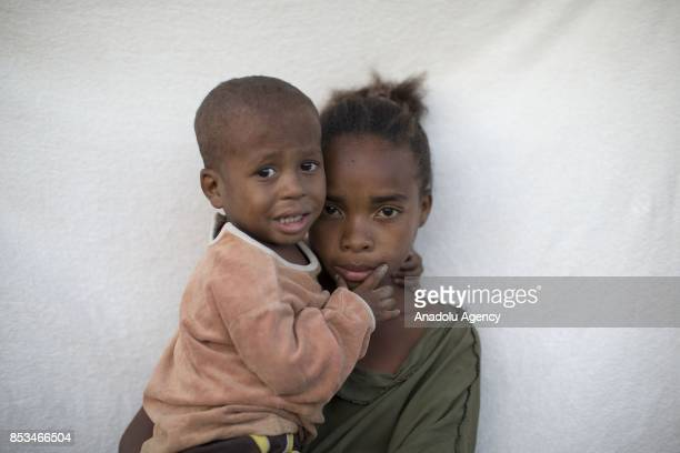 9yearold Gina holding her brother in her arms poses in Antananarivo Madagascar on September 24 2017 In Madagascar most of the girls with no education...