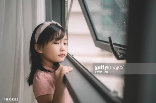 彼女の寝室の窓から外を見ているアジアの中国の幼い子供 - 見つめる ストックフォトと画像
