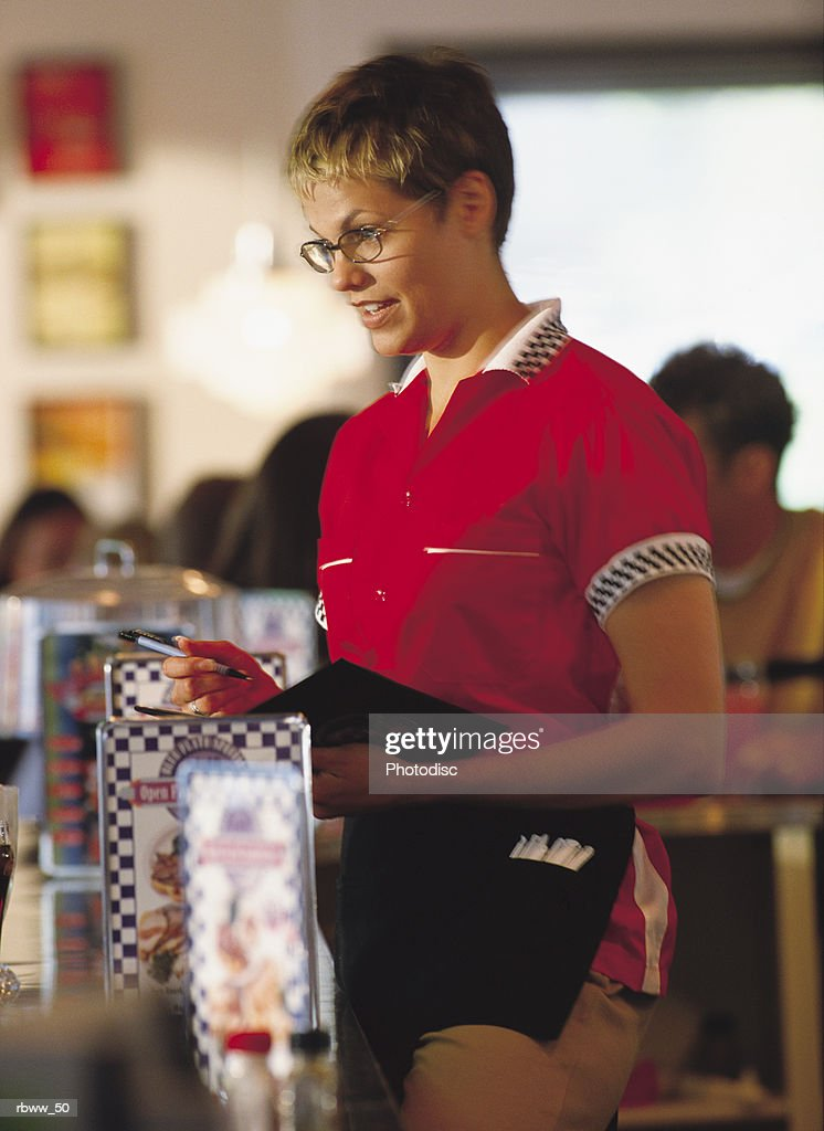 a attentive waitress takes an order at a diner : Foto de stock