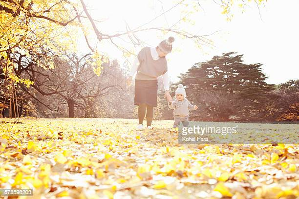 a baby and mother playing in the park in autumn