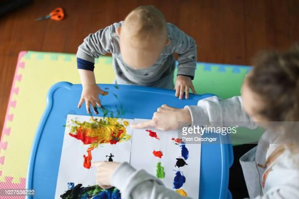 a baby boy finger painting with his mother. - dama de companhia - fotografias e filmes do acervo