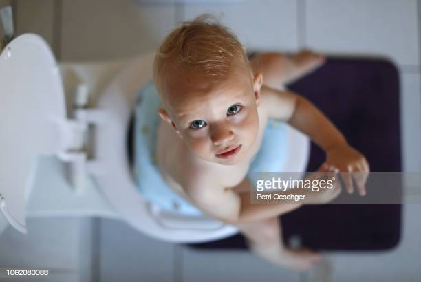 a baby boy learning how to use the toilet. - defecare foto e immagini stock