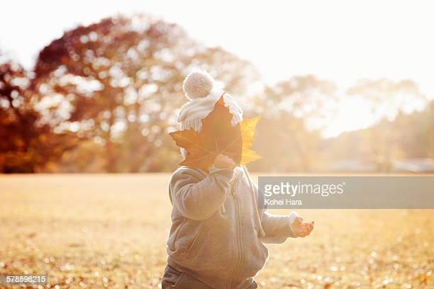 a baby playing in the park in autumn