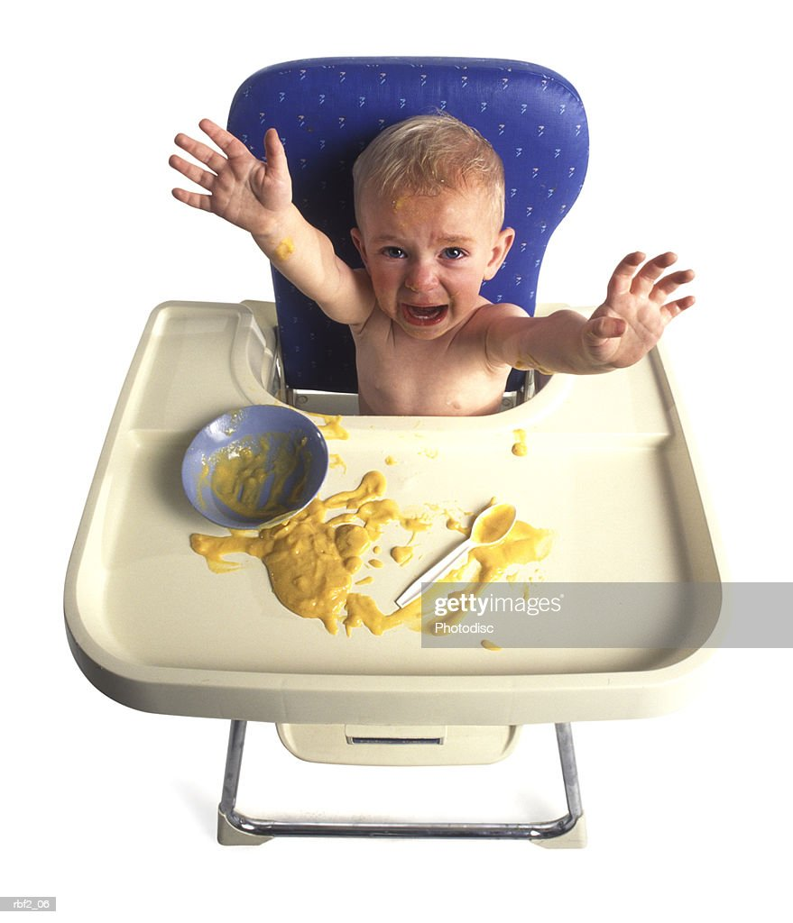 a baby sits in his high chair as tosses his baby food around : Stockfoto