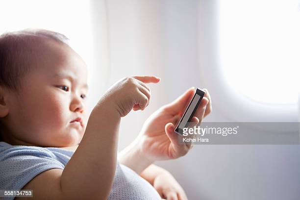 a baby using a smart phone on air plane