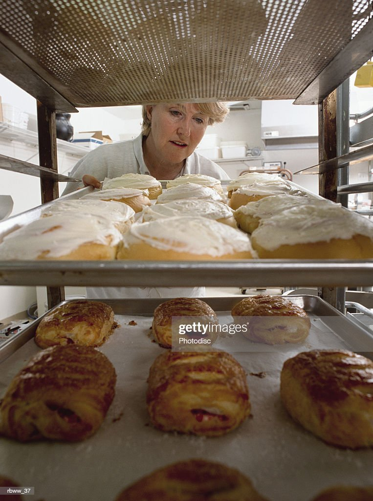 a baker inspects a fresh batch of pastery and breads : Foto de stock