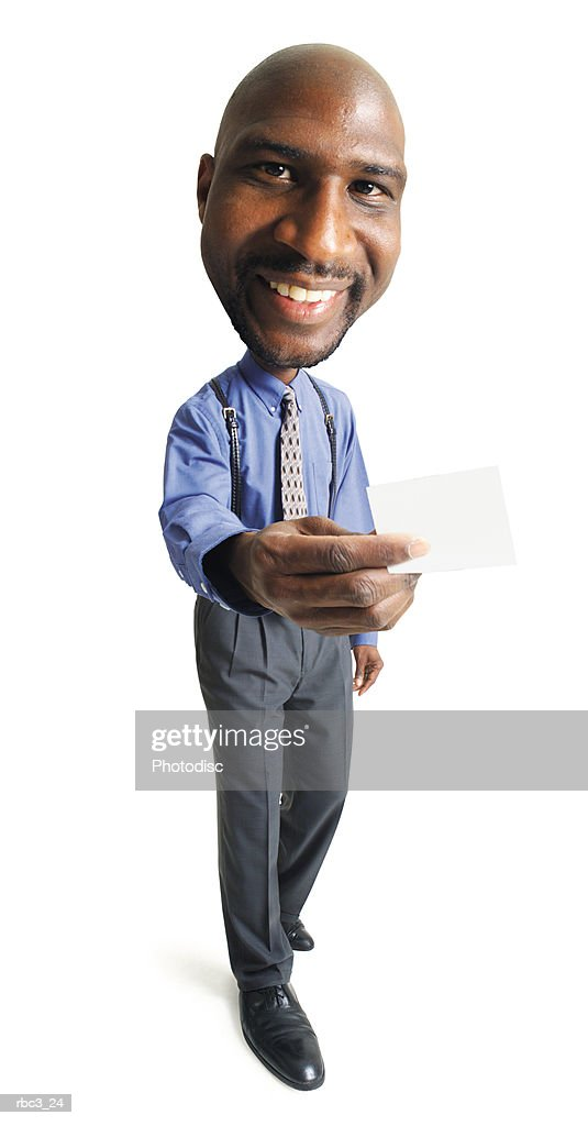 a bald african american male in a blue shirt and tie stands smiling as he hold out a blank business card : Stockfoto