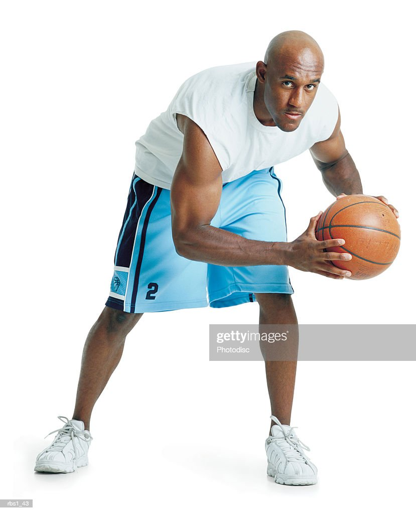 a bald african american man dressed in powder blue basketball shorts and is leaning forward holding a ball preparing to pass : Foto de stock