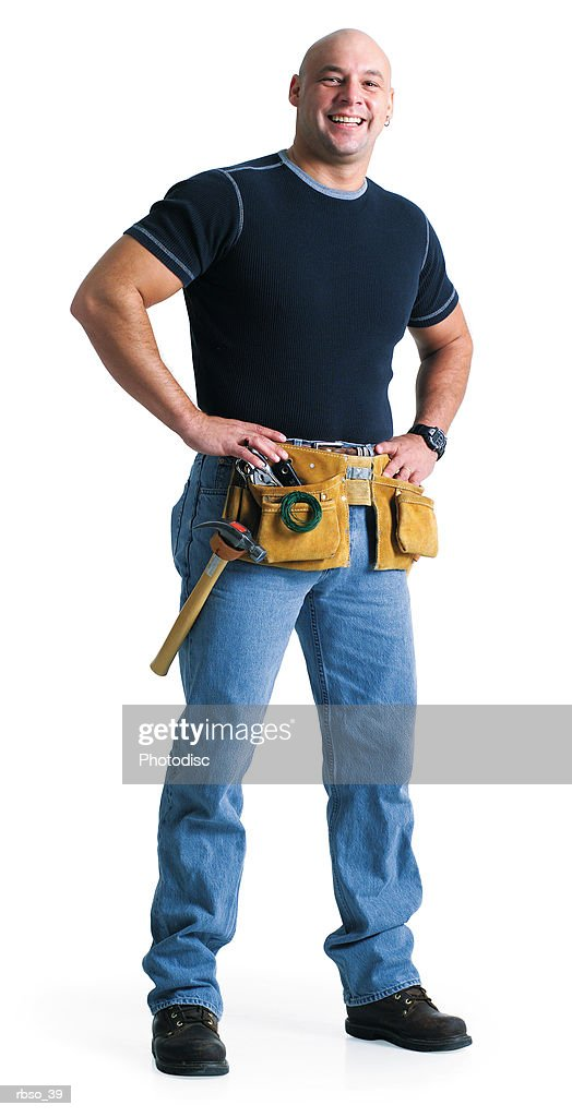 a bald caucasian male builder wearing a tool belt puts his hands on his hips and smiles : Foto de stock