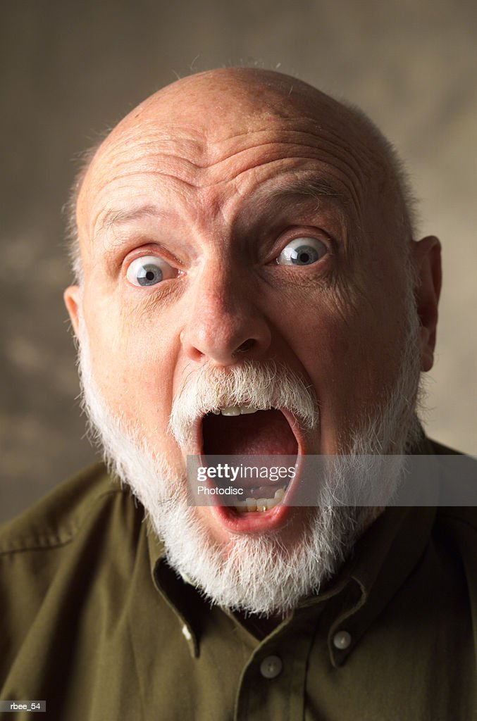 a bald elderly caucasian man with a white beard is wearing a dark dress shirt and screaming wide eyed : Photo