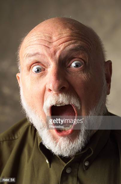 a bald elderly caucasian man with a white beard is wearing a dark dress shirt and screaming wide eyed