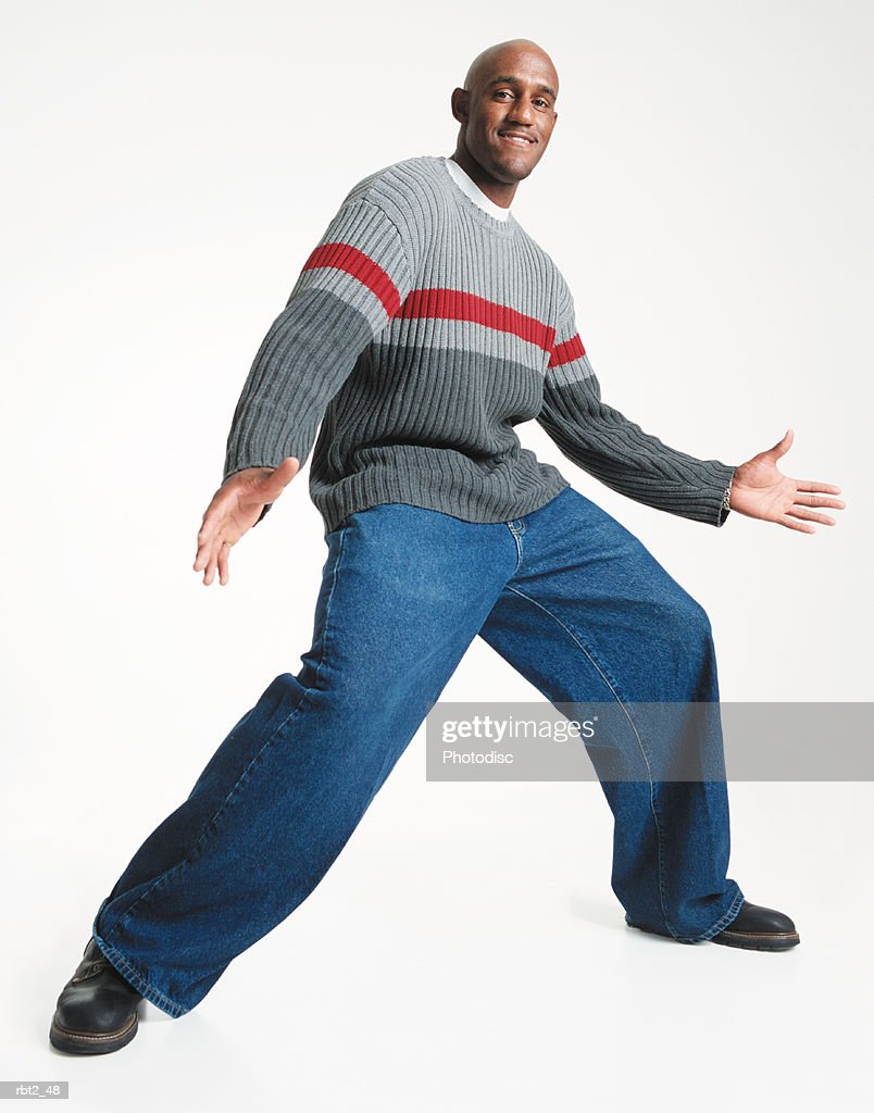 a bald young african american man in baggy jeans and gray sweater strikes an animated pose with arms and legs spread wide while looking toward the camera : Foto de stock