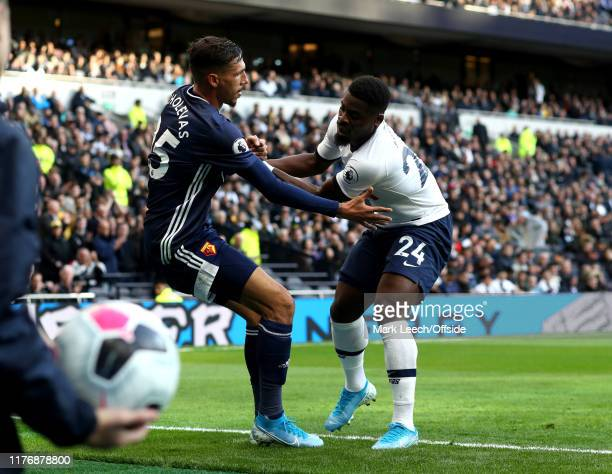 a ballboy waits to return the ball as Jose Holebas of Watford and Serge Aurier of Tottenham pick themselves up during the Premier League match...