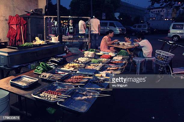 A barbecue in Chinese street that foods of all and sundry are put in front of you in stainless steel plates.