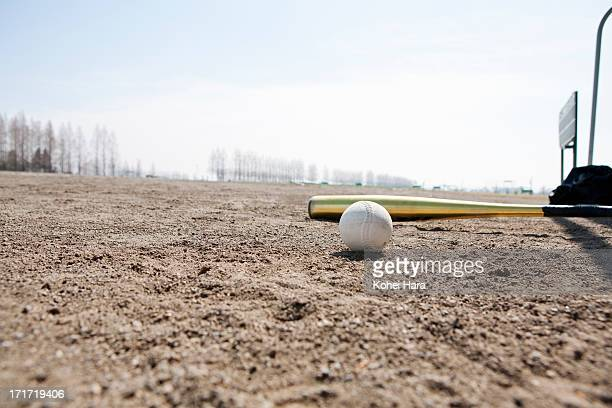 a baseball and a bat on the ground