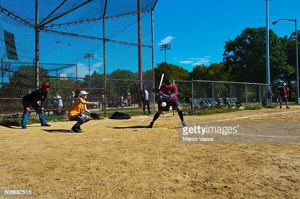 a baseball match between friends on a sunny saturday morning in McCarren park Brooklyn N