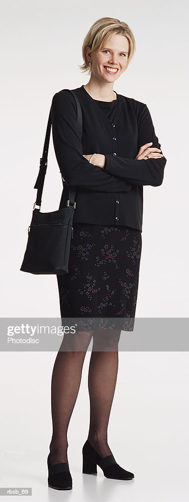 a beauiful young caucasian woman with shoulder length blond hair dressed in a dark blouse and skirt with a purse on her shoulder smiling into the camera : Stockfoto