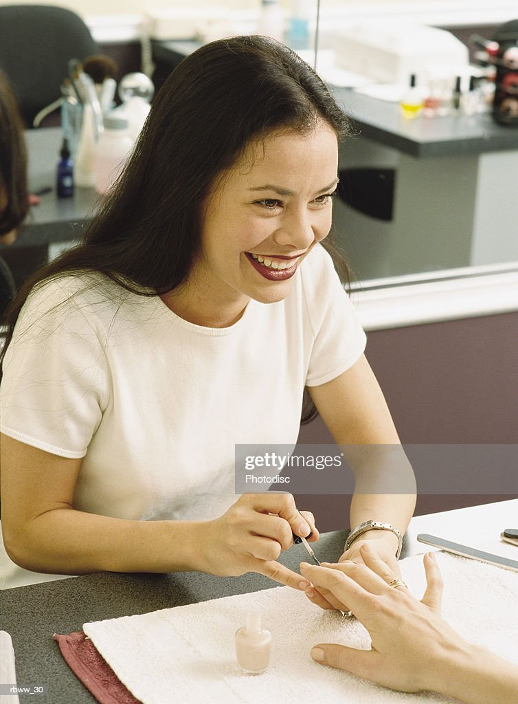 a beautician pauses to laugh with a customer as she works on her nails : Foto de stock