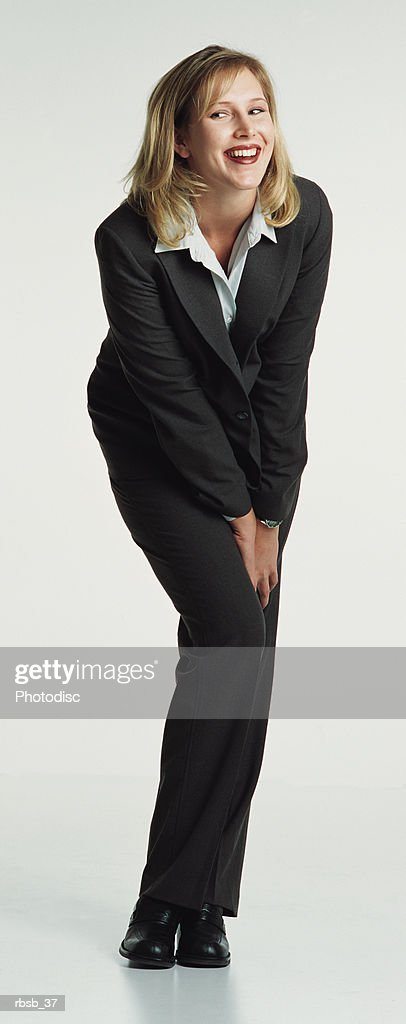 a beautiful blond caucasian woman with shoulder length hair is dressed in a dark business suit while crouching down with her hands between her knees in a flirtatious gesture : Foto de stock