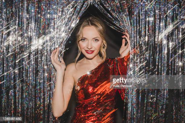 a beautiful blonde girl in a red shiny dress celebrates the new year rejoices smiles lights sparklers drinks champagne - holiday stock pictures, royalty-free photos & images