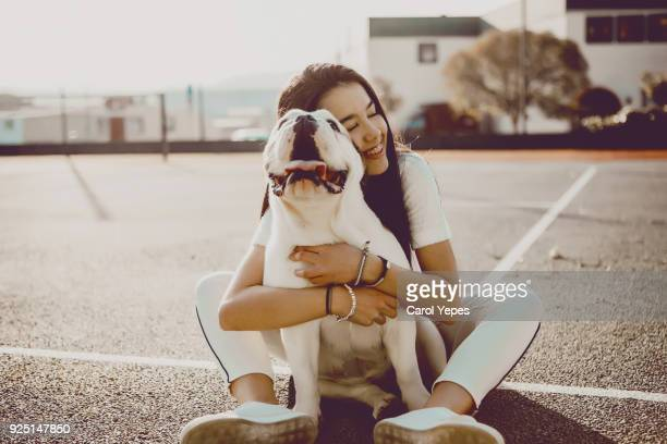 a beautiful brunette teen girl  hugging english bulldog - pet owner stock pictures, royalty-free photos & images