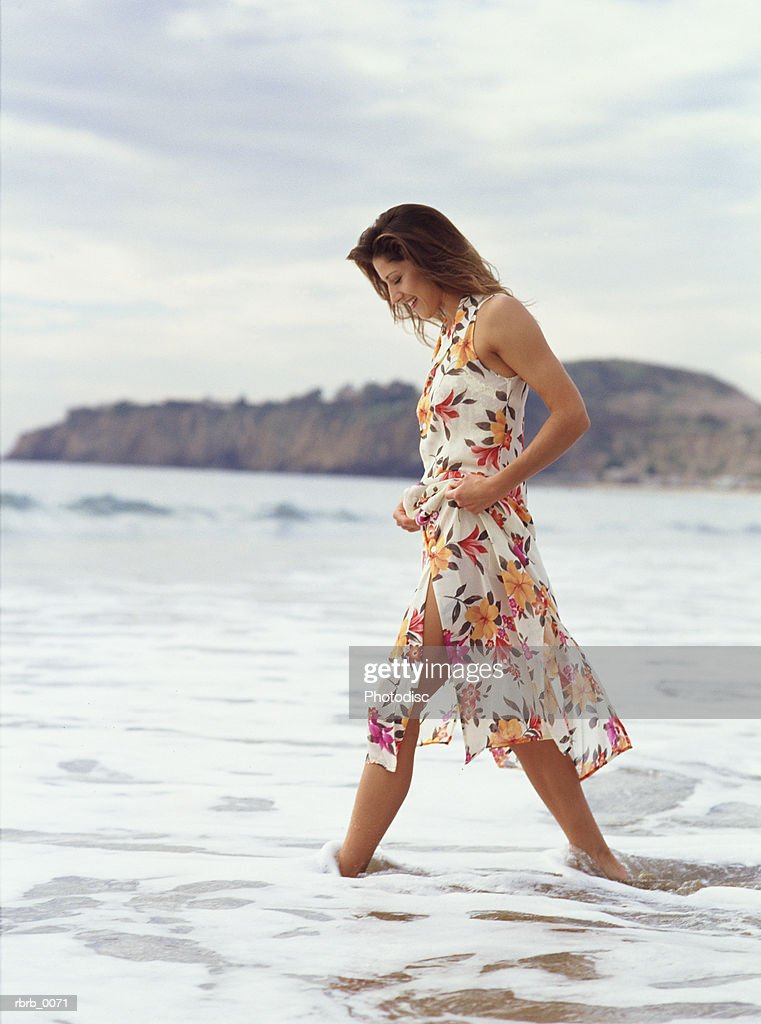 a beautiful caucasian woman walks along a tropical ocean shore : Foto de stock