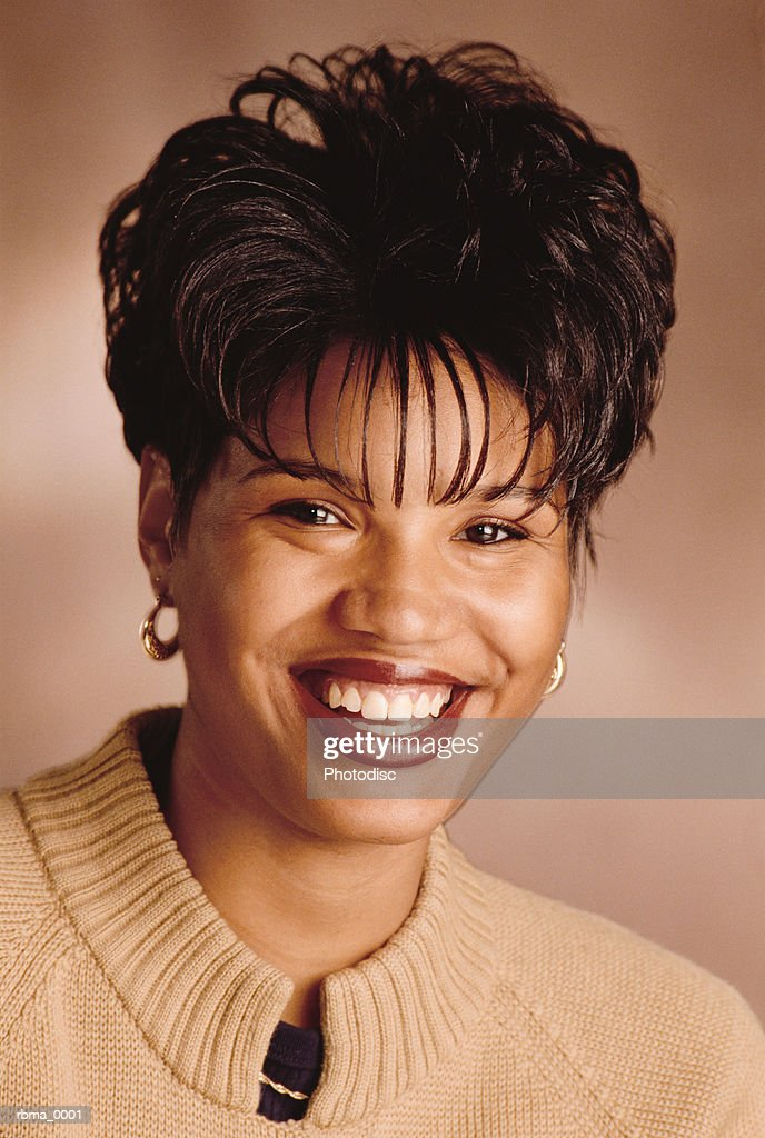 a beautiful happy african american woman in a tan sweater laughs and smiles for the camera : Stockfoto