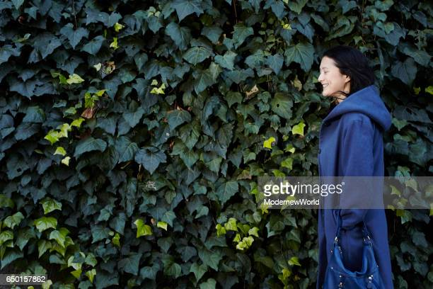 a beautiful lady's side view with her blue coat - 優美 ストックフォトと画像