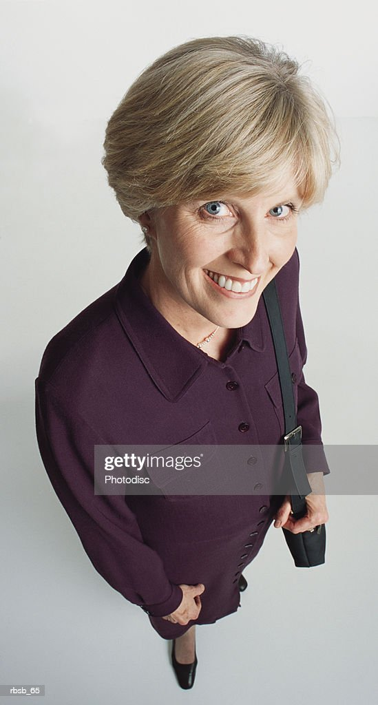 a beautiful middle aged caucasian woman with short blond hair and blue eyes dressed in a purple dress and black purse looking up into the camera : Foto de stock