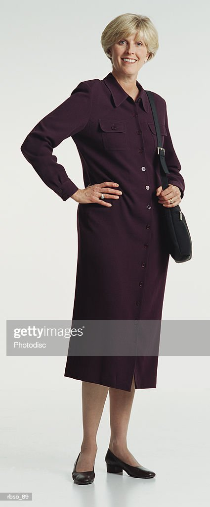 a beautiful middle aged caucasian woman with short blond hair and blue eyes dressed in a purple dress and black purse looking  into the camera with her hands on her hips : Foto de stock