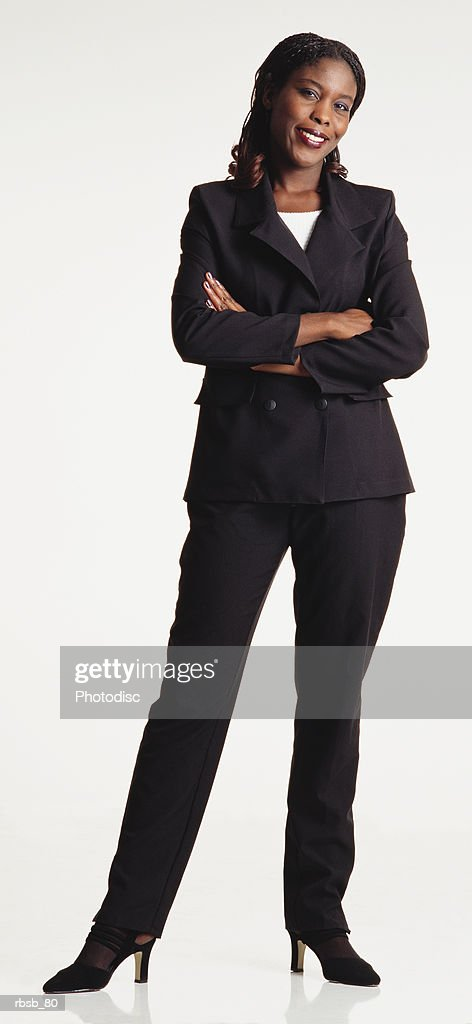 a beautiful young african american woman with long hair dressed in a dark black suit standing looking into the camerawith her arms crossed : Stockfoto