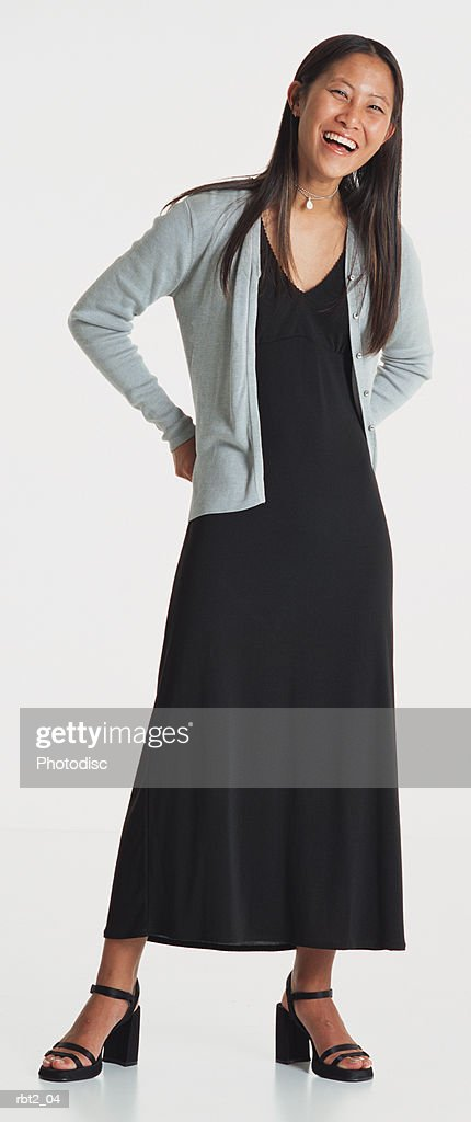 a beautiful young asian woman wearing a long black dress stands laughing with her hands on her hips : Foto de stock